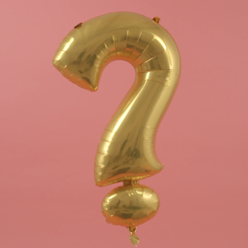 a gold helium balloon in the shape of a question mark on a pink background