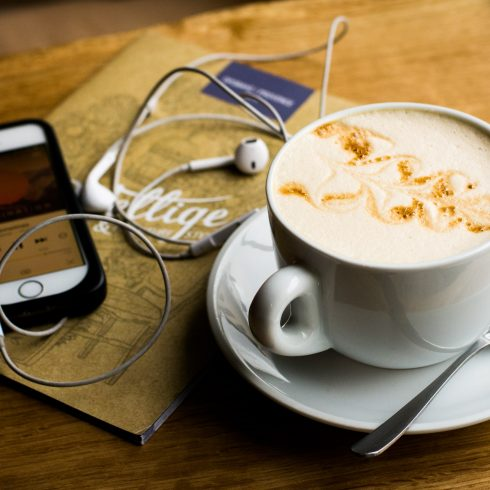 an iphone with headphones resting on a book beside a latte in a white mug