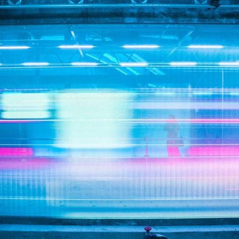 train speeds past platform in a blue and pink blur